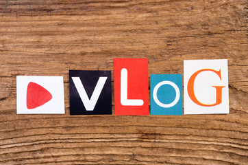 "Word ""Vlog"" in cut out magazine letters on wooden background"