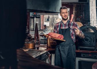 A man holds beef steak on a kitchen.