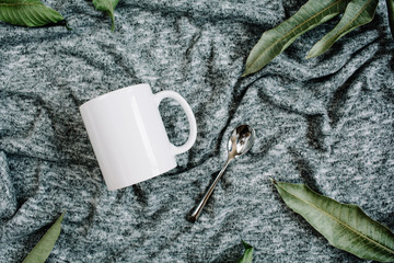 Blank template of white mug, spoon and green leaves on grey textile background. Flat lay, top view.