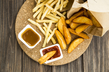 fried potatoes and french fries in paper bags with ketchup and sweet and sour sauce. junk food.