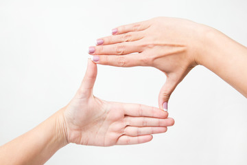 Close up of female caucasian hands isolated on white background. Young woman forming frame with her two hands as if looking at something virtual and invisible. Point of view shot.