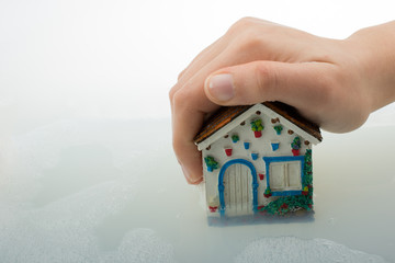 Model house in hand in foamy water