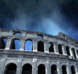 Flavian Amphitheatre or Colosseum in Rome with night sky in the background, Italy.