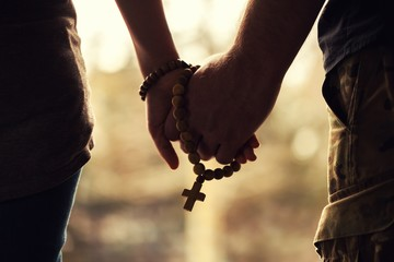 Holding rosary in hand.