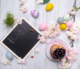 Easter cake with colored eggs and board for chalk