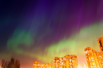Aurora borealis starry night over the city and houses