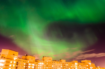 Aurora borealis green starry night over the city and houses