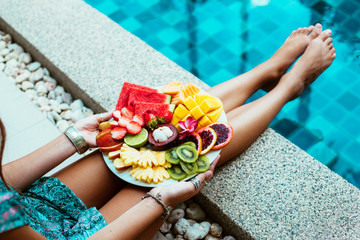 Relaxing with fruits by the pool