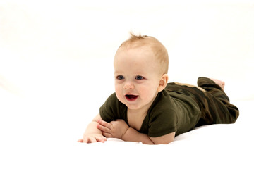 Smiling infant child lying on the white blanket
