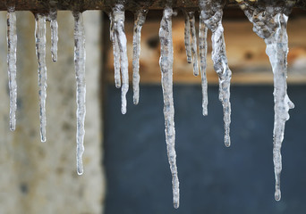 a variety of long icicles hanging on a rusty pipe