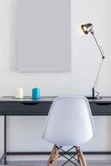 Small office desk with white chair and single lamp