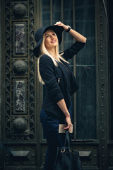 Happy blonde young woman holding leather handbag and bronze smartphone, posing from profile. Dressed in businesswoman suit and smiling cheerful in front of Gothic wooden door.