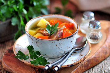 Fish soup with potatoes, carrots and parsley on the old wooden background.