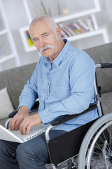 senior in wheelchair using a computer