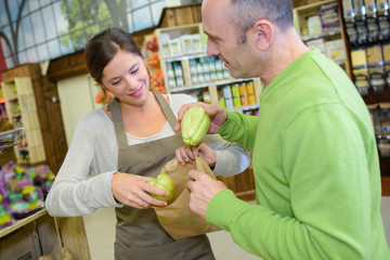Shop assistant helping man put fruit in paper bag