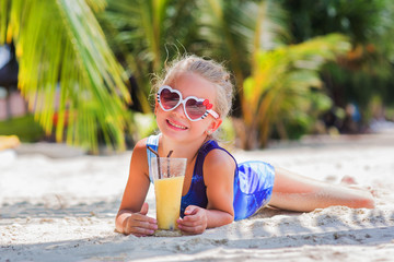 little cute girl on the sand at the beach in sun glasses with a glass of exotic cocktail juice