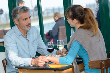 Couple holding hands across restaurant table