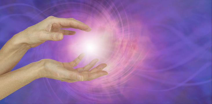 White Orb Energy Between Hands - a pair of female hands with a white energy orb between on an ethereal pink and purple vortexing energy field background