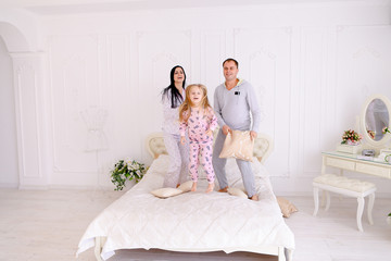 Portrait of family fighting pillows, jumping on bed together in