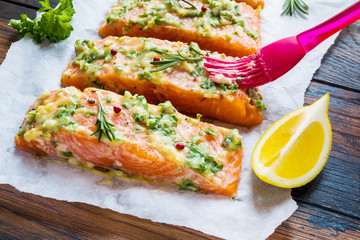 A process of cooking, pieces of raw salmon have been coated by garlic herb butter mixture on parchment paper, wooden table.