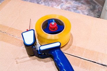 Packaging tape gun dispenser on a cardboard box