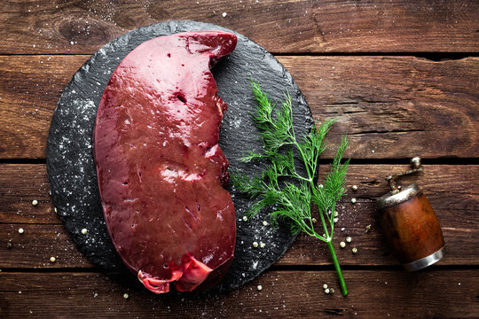 Raw liver on slate board on wooden background top view