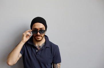 Macho brutal man with latin skin and tattooed hands portrait in studio on neutral fone. Strong and brave guy in sunglasses look to the camera,Copy space for pomotion content.Confident and calm emotion