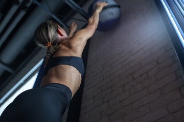 Woman doing wall ball exercise at gym