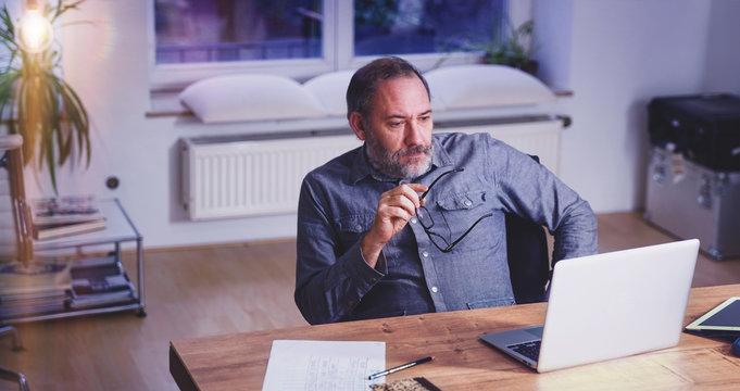 Grey Bearded mature man creative director sitting in modern office