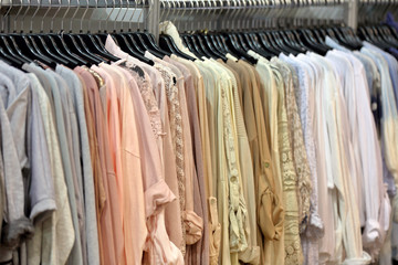 Row of clothes hanging in wardrobe or store