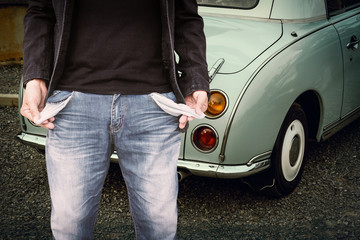 Man showing his empty pockets with classic car background.