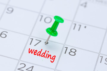 wedding written on a calendar with a green push pin to remind you and important appointment.