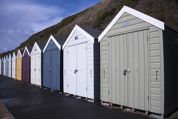 Row of colourful beach huts on beach promenade in front of cliffs