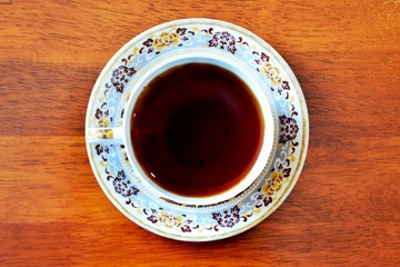 Cup of black tea on wooden table, top view