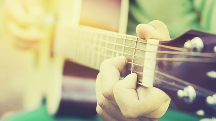 Relaxing Musical concept,Practicing in playing guitar. Handsome young men playing guitar,man's hands playing acoustic guitar, close up,selective focus,vintage color....