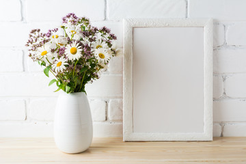 White frame mockup with blooming wildflower bouquet near painted brick wall