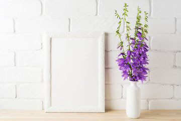 White frame mockup with purple campanula bouquet near brick wall