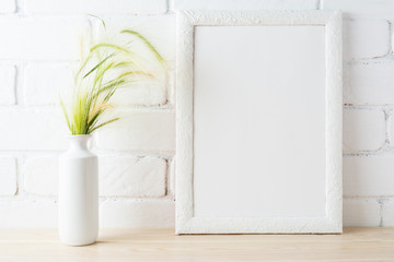 White frame mockup with wild grass ears near painted brick wall