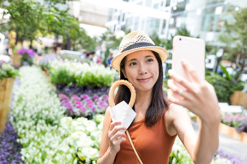 Woman holding Spanish churro to take selfie by cellphone