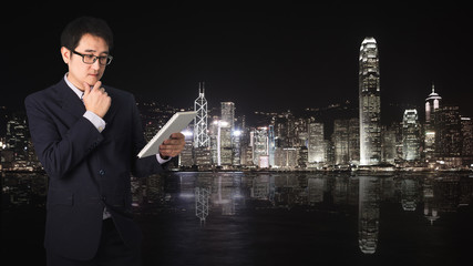 Double exposure Confident Asian businessman reading notebook or document file with cityscape on blurred building.