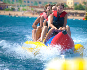 People ride on banana boat
