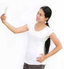 Asian girl taking pictures of herself through cell phone on white background