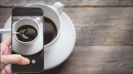 Taking a photo by Finger Pressing on Smartphone for Photograph Close up Hot Coffee on wooden with Copy Space in Chill and Relax Concept, Image for Coffee Advertise or Social Media with Drink Concept