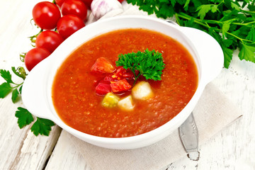 Soup tomato in white bowl with vegetables and parsley on board