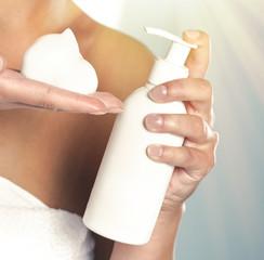Female hands using cosmetic liquid soap close up