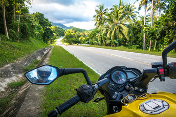 View of the open jungle road from yellow motorbike