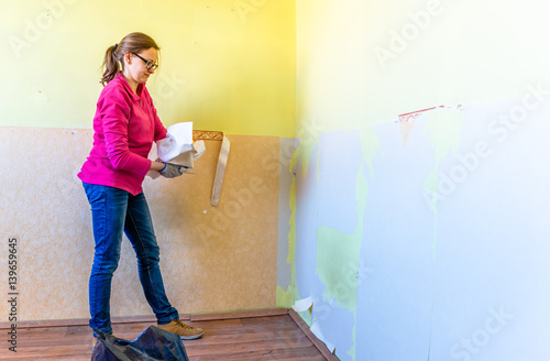 Woman Removing Old Wallpaper From The Wall Home Renovation Conc