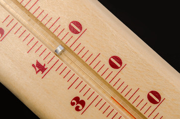 Wooden thermometer on a black background