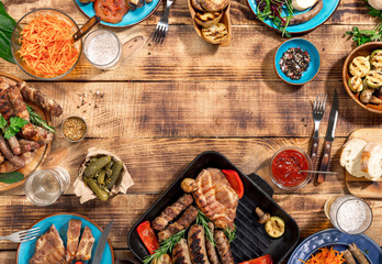 Barbecued steak, sausages and grilled vegetables on wooden picnic table