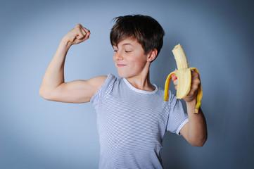 Starker Junge mit Banane zeigt seine Muskeln